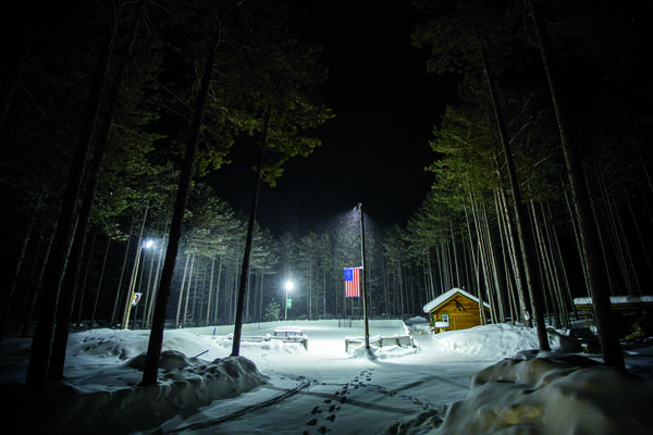 An outdoor ice rink surrounded by trees.