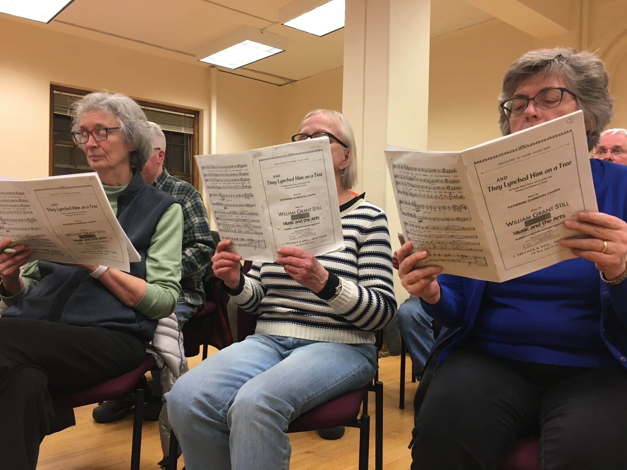 People sit in a row reading music and singing.