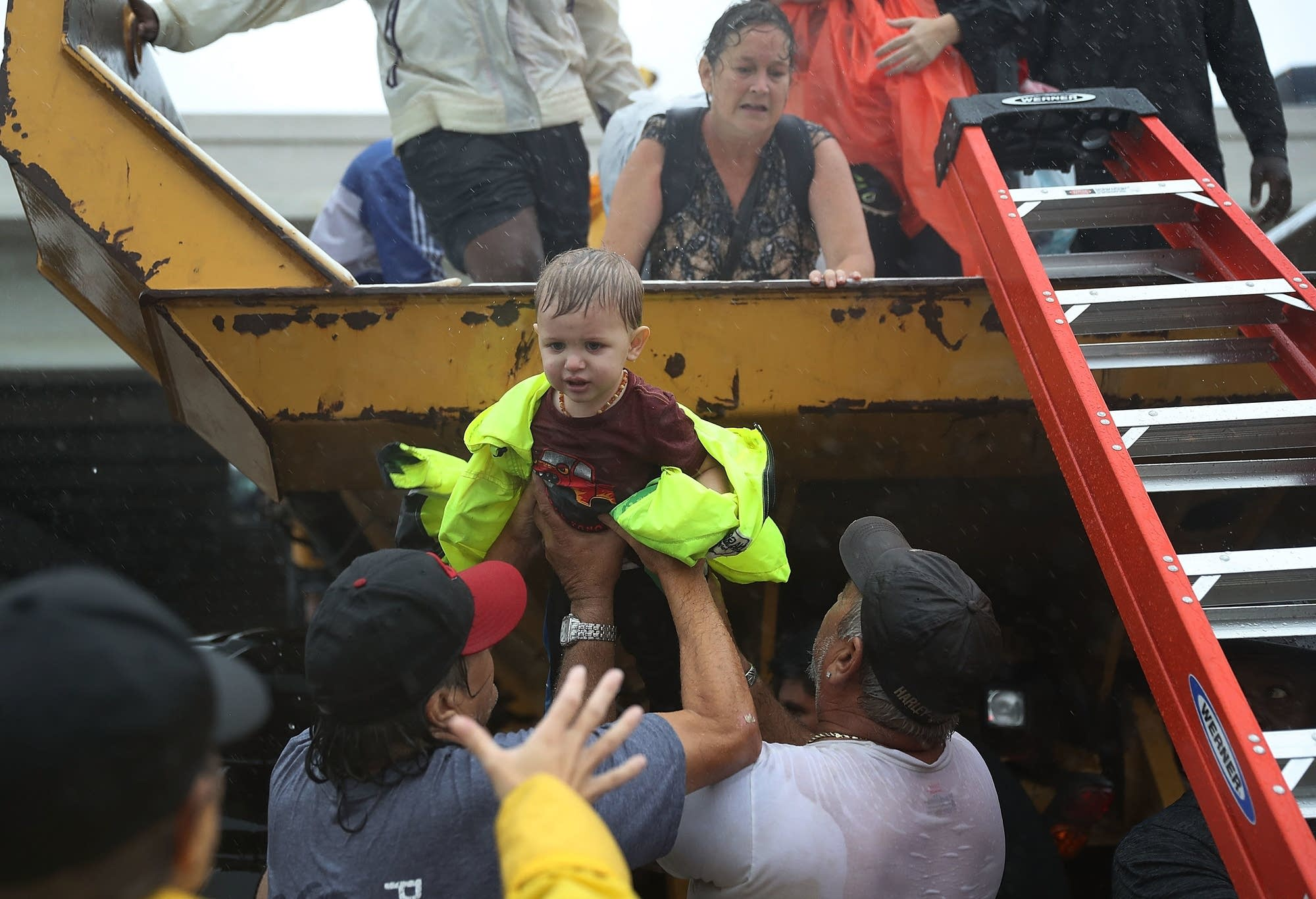 A child is helped off the back of a rescue truck.