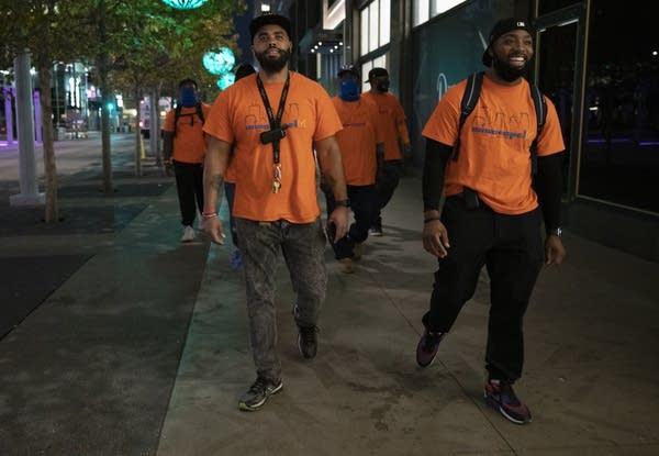 A group of people wearing orange shirts walk down a sidewalk.