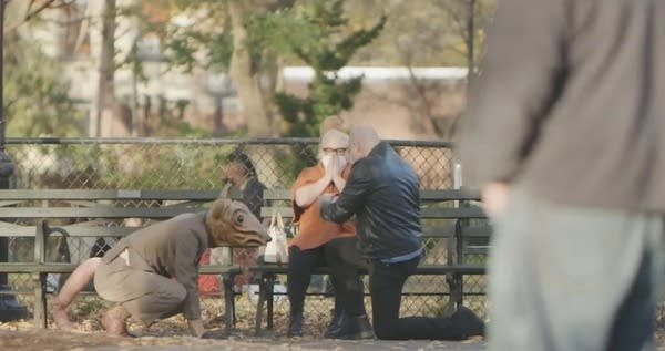 Man dressed as rat next to a man on one knee proposing to woman in park