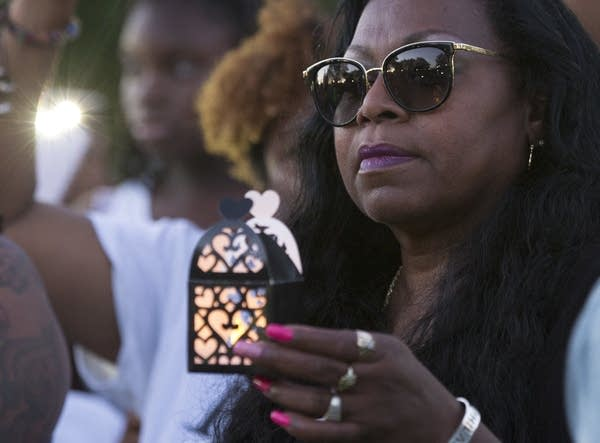 Valerie Castile holds a lantern during Pastor Danny Givens' speech.
