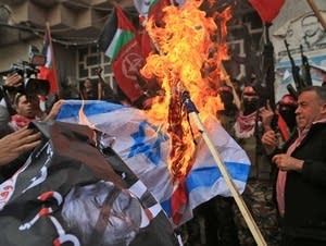 Palestinian protesters burn the Israeli flag and a poster of Trump.