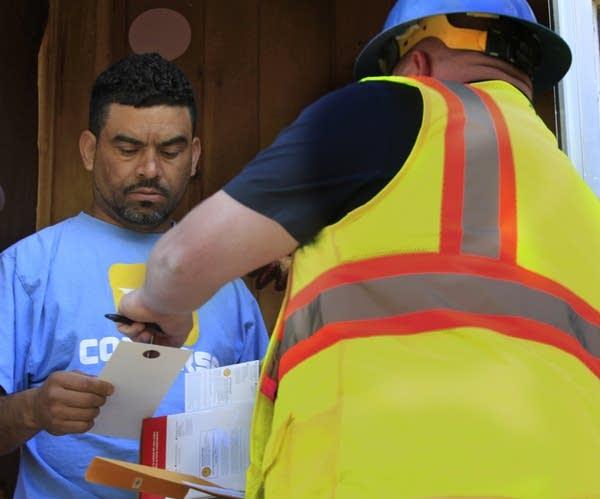 Homeowner Ronald Mendoza listens to instructions.