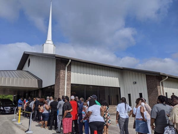 Lines of mourners wait outside a church