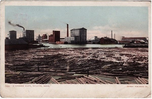 A vintage postcard of logs and mill in Duluth