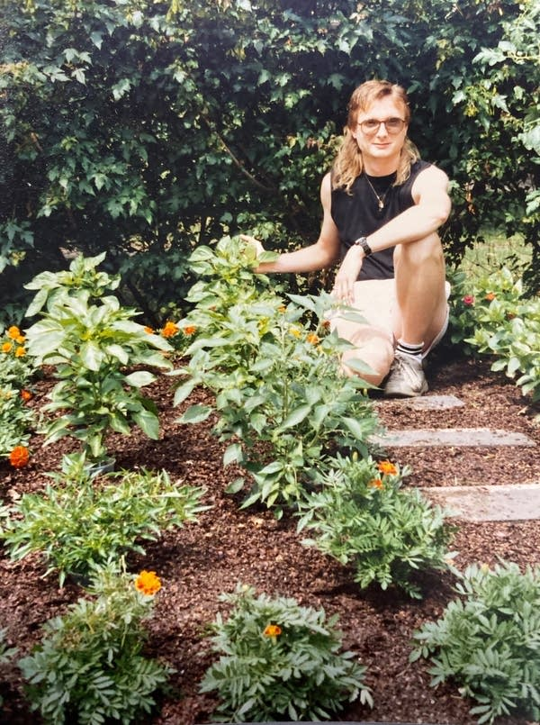 A man in shorts and tank top kneels in a garden.
