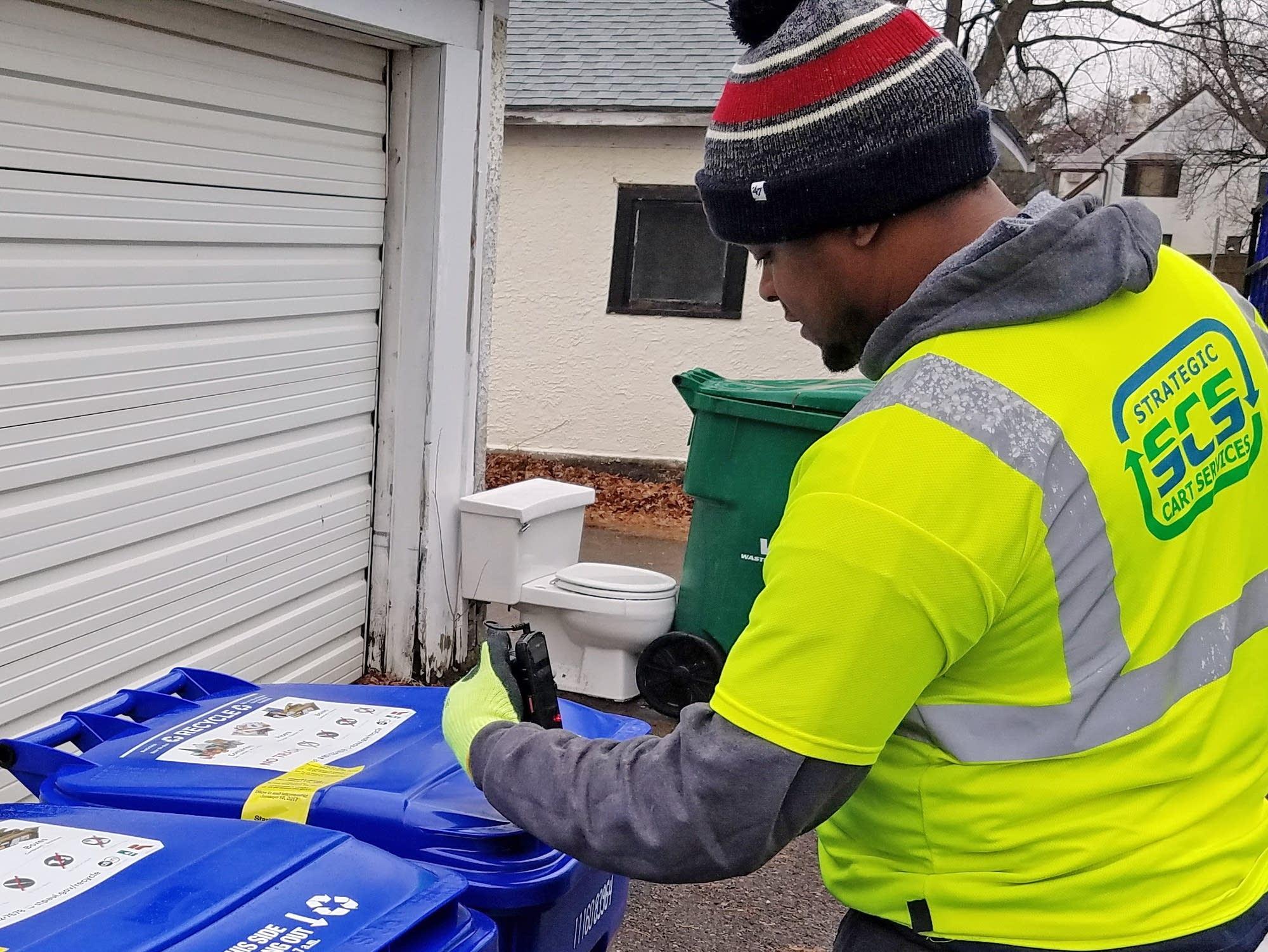 A worker scans a recycling bin in St. Paul.