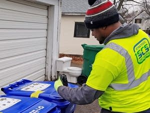 A worker scans a recycling bin in St. Paul.