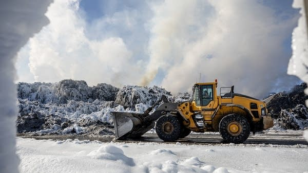 A front loader in front of a large pile of ice-covered cars.