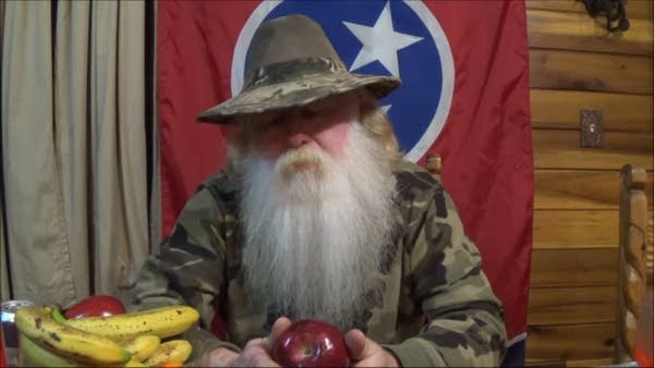 "Mark ""Coonrippy"" Brown with a long white beard holding an apple"