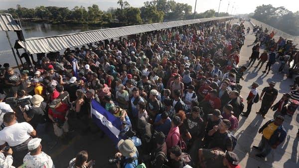 Migrants line up behind an Honduran flag at a border crossing
