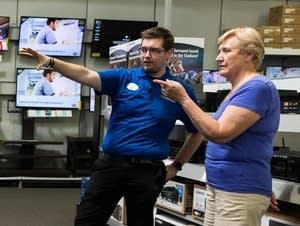 Best Buy employee James Feltes gives shopper Barbara Lee information.