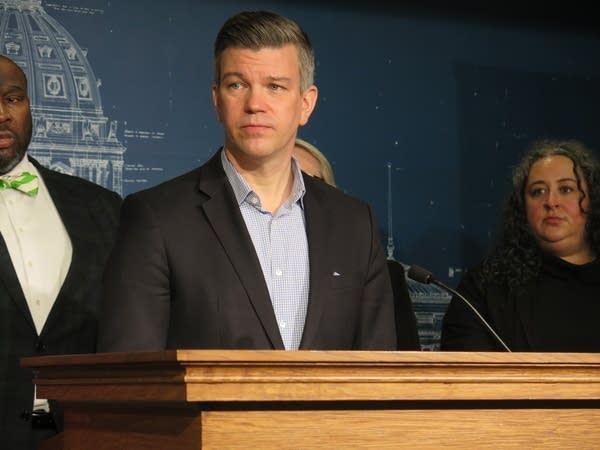lawmaker stands at podium