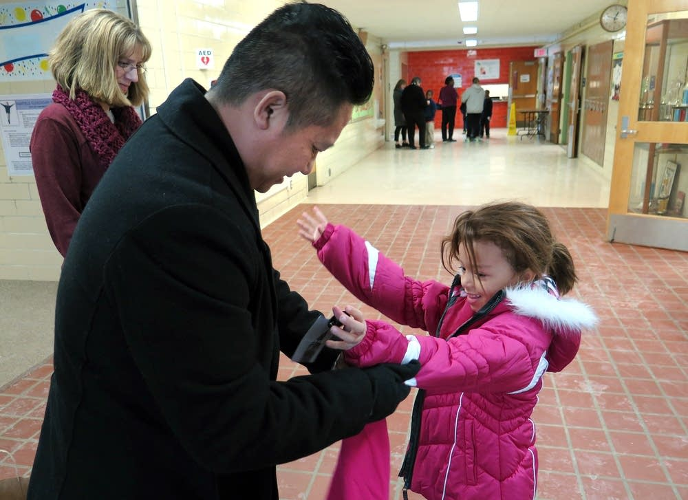Wijit Xiong helps Brittany with her new coat.