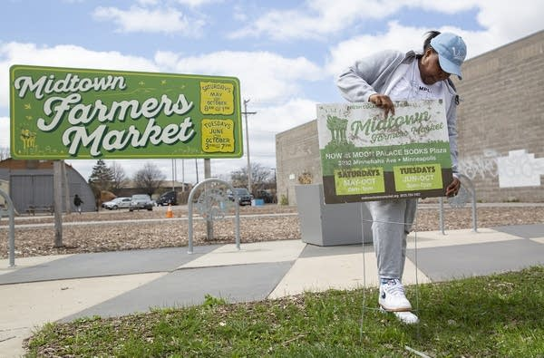 "A woman puts up a sign that reads ""Midtown Farmers Market."""