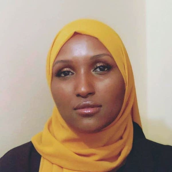A woman wearing a yellow hijab and black shirt.