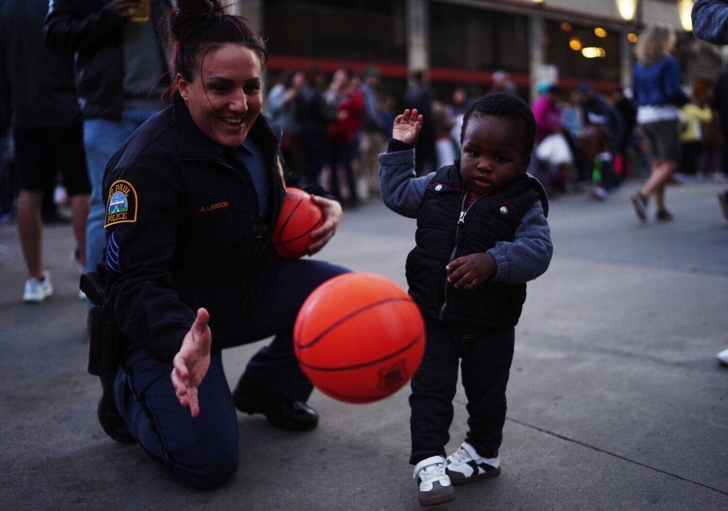 St. Paul Police Sgt. Amber Larson plays with 18-month-old Evance