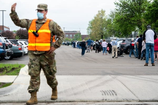 A man in fatigues and a vest directs traffic.