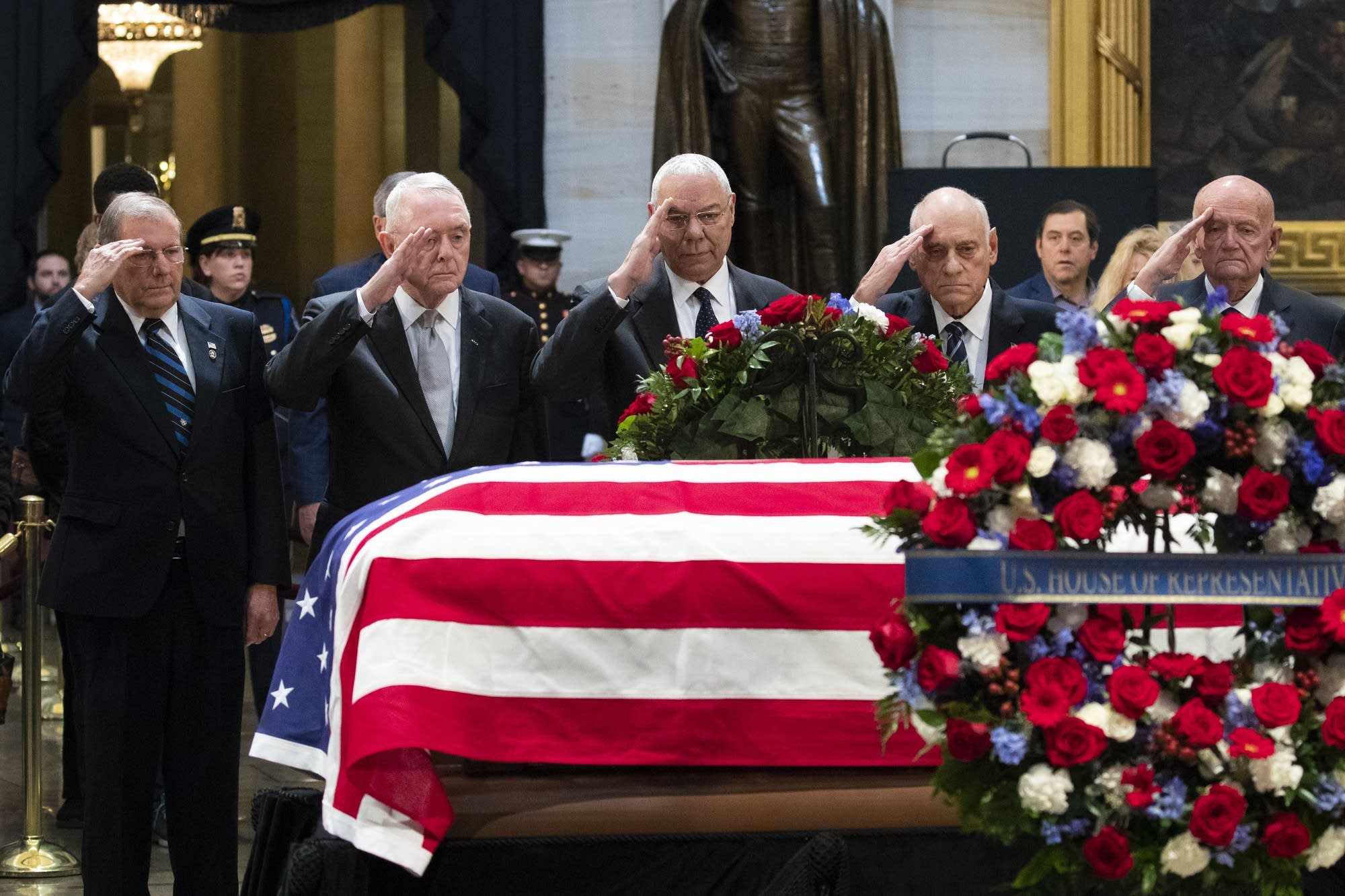 Colin Powell and former military officials salute former President Bush.