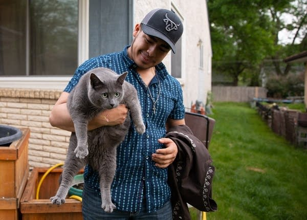 a young person holds a cat