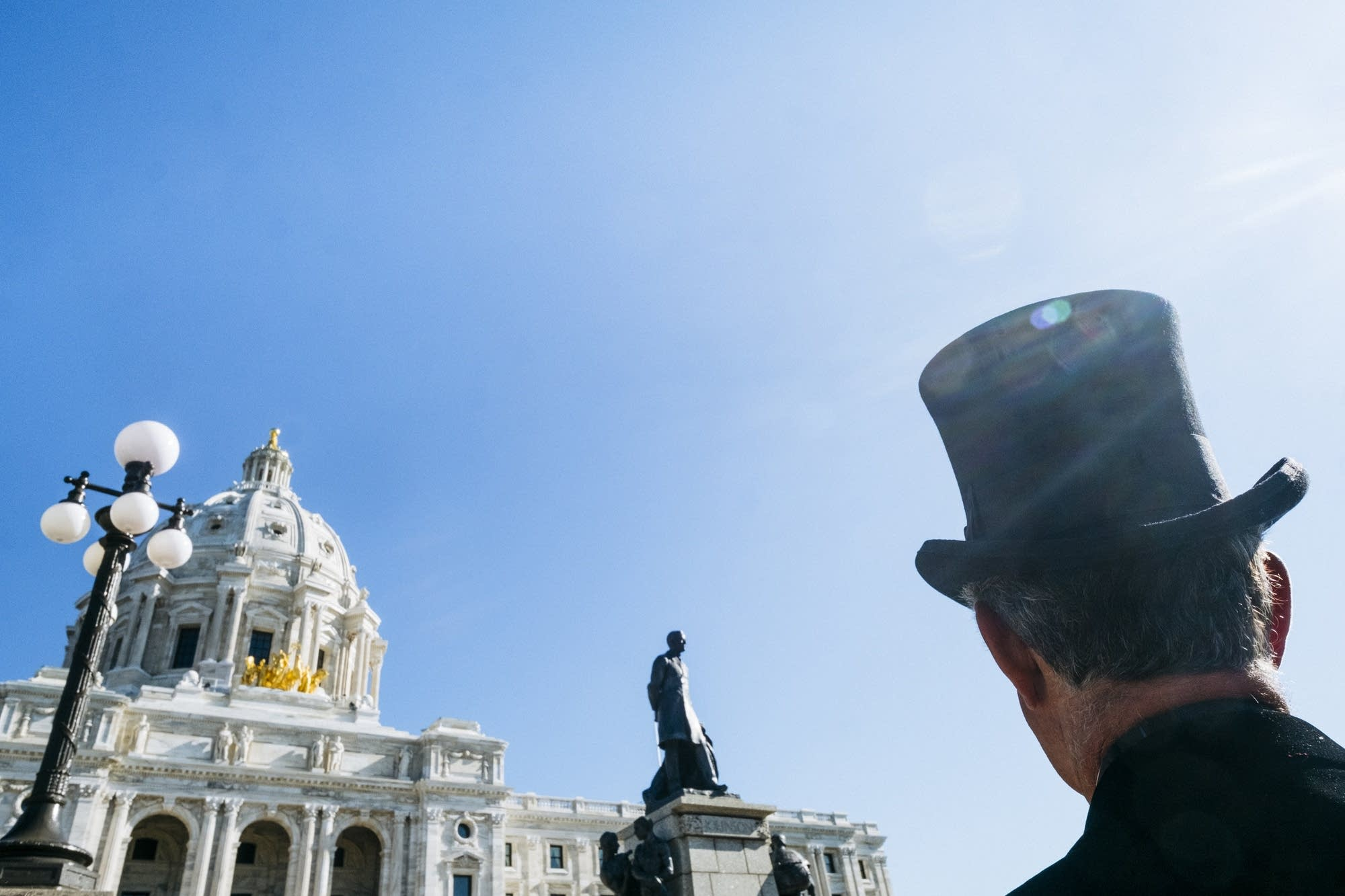 A man in a top hat watches the ribbon cutting.