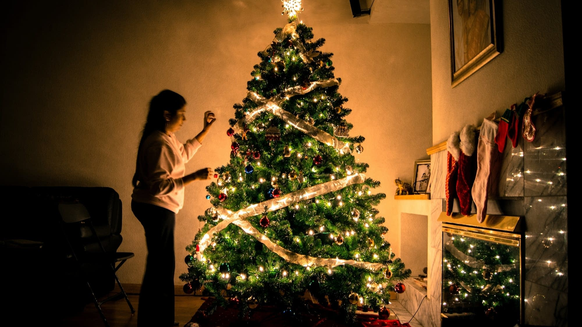 A young girl decorates a Christmas tree.