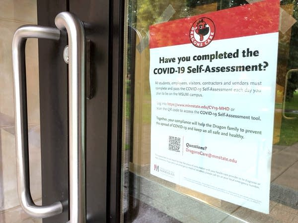 """A sign on a door reads """"Have you completed the COVID-19 self-assessment"""""""