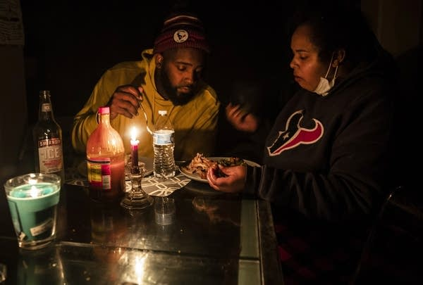 A man and woman eat dinner by candlelight after their power goes out.