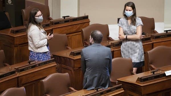 Three state representatives talk while wearing masks.