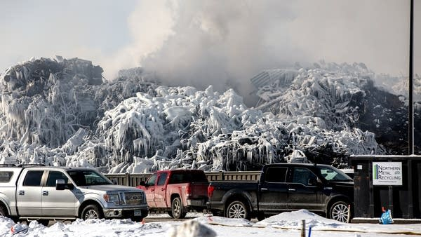Smoke billows over a pile of ice-covered cars.