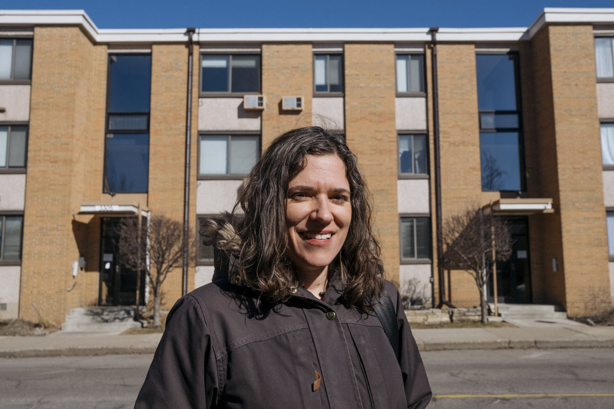 Lisa Bender stands for a portrait in front of an apartment building.