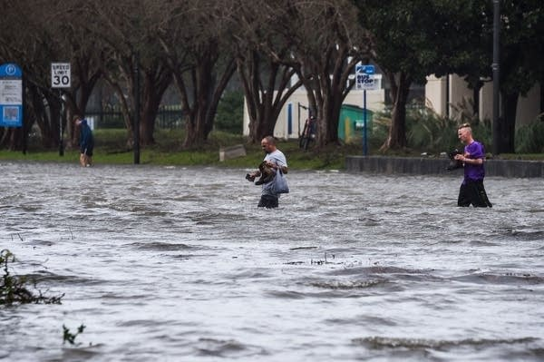 People cross a flooded street.