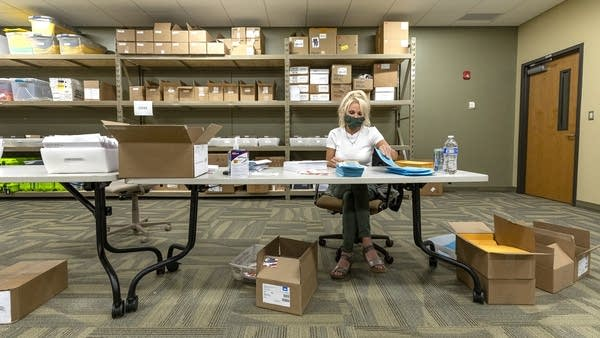 A woman sits at a folding table while wearing a mask, surrounded by boxes.
