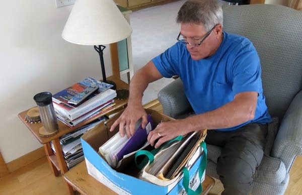 Mike Foy thumbs through a box of his old files.