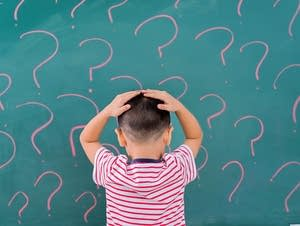 A boy in front of blackboard with question marks.