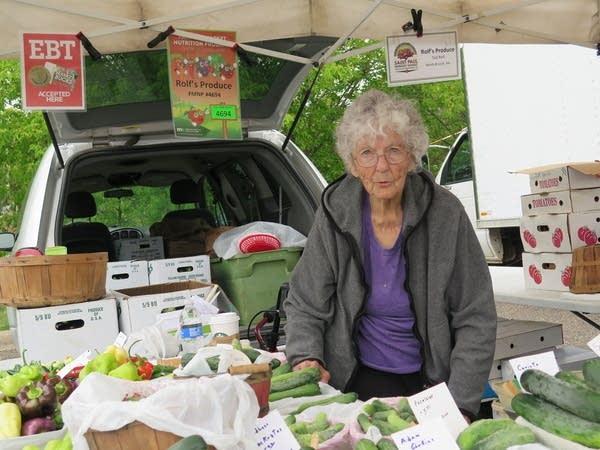 A woman sells vegetables at a farmer's market.