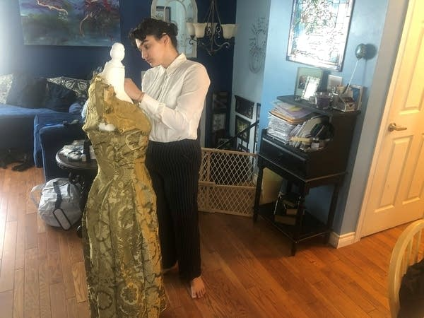 A person makes alterations to a dress.