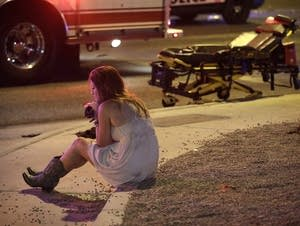 A woman sits on a curb after the Las Vegas shooting.