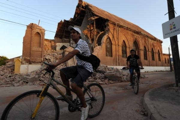 Cyclers pass by destroyed church