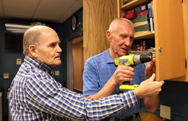 Phil Johnson holds a cabinet door as Lyle Wandrei drills a new handle.
