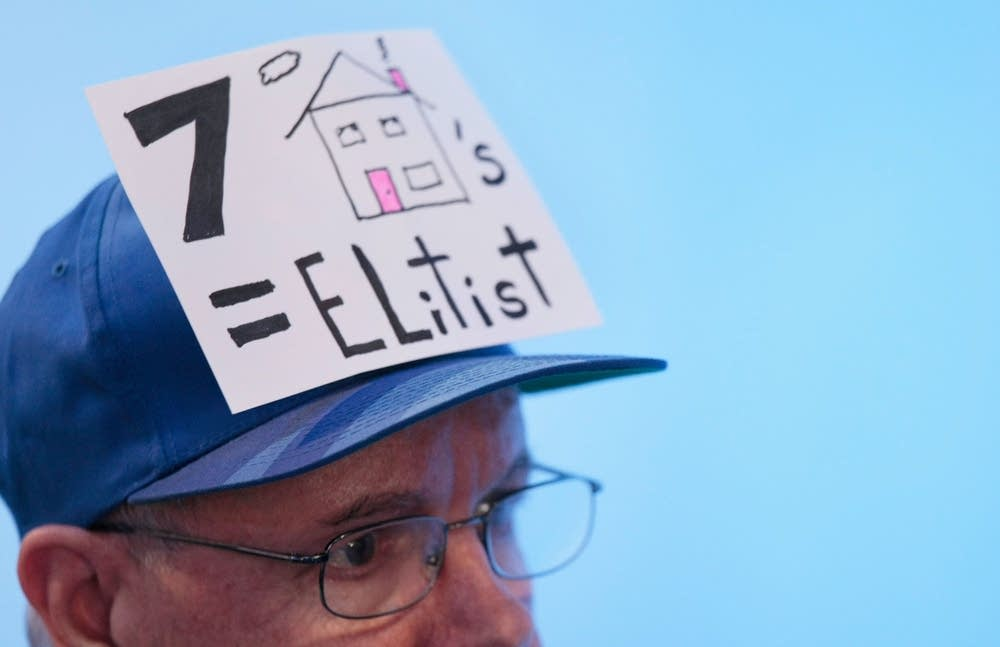 A man wears a hat referencing McCain's houses