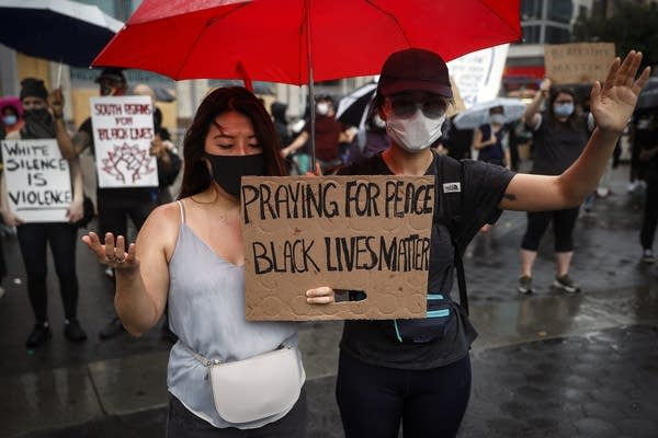 Protesters pray in the rain for a rally in New York.