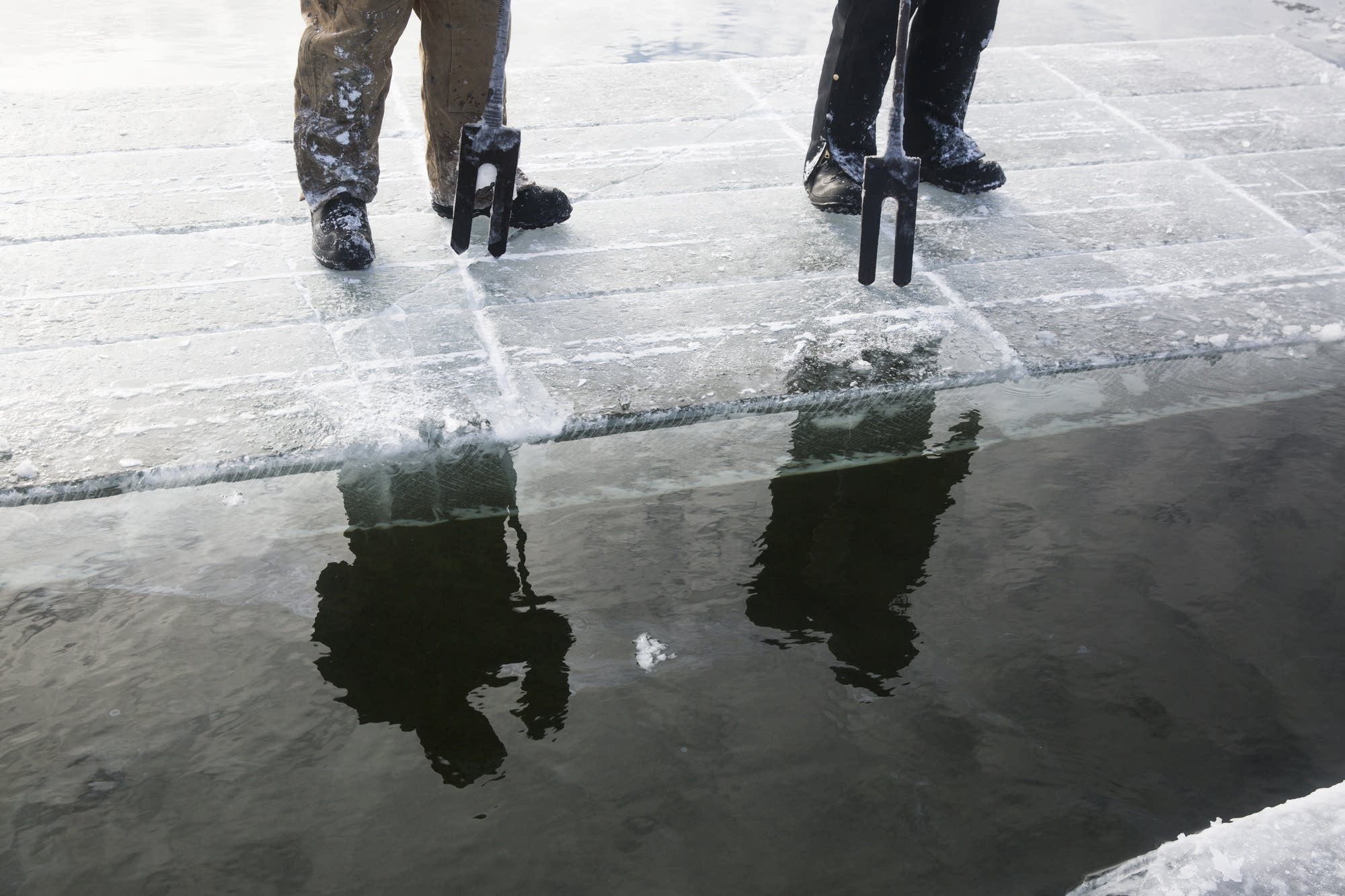 Two Wee Cut Ice workers and their chisel tools are reflected in the water.