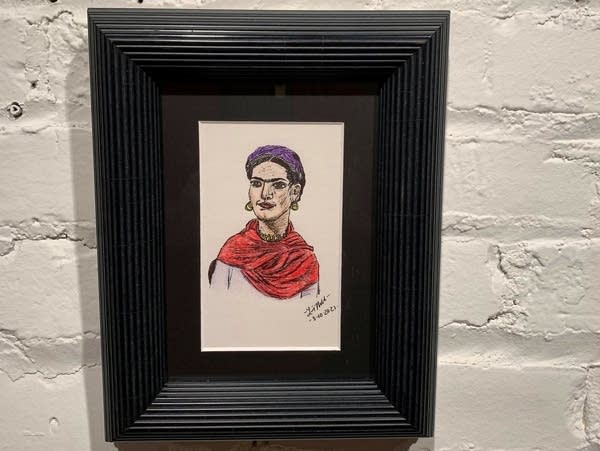 A portrait of Frida Kahlo hangs on a wall.