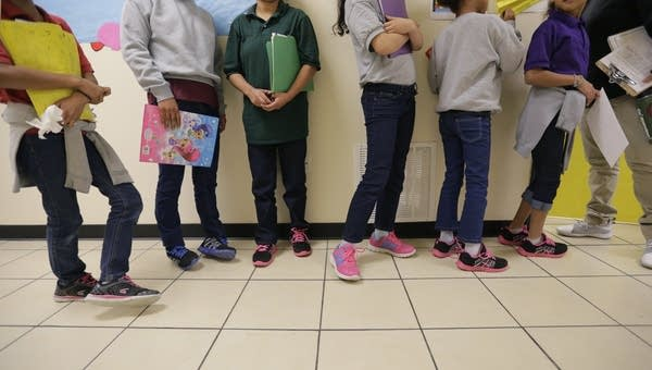 Migrant teens line up for a class