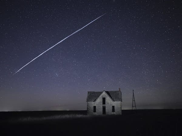 A string of satellites passes over an old house