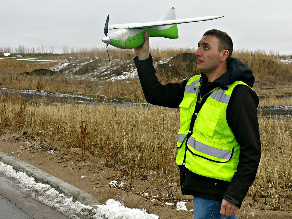 Joey Schmit launches a small fixed-wing drone.