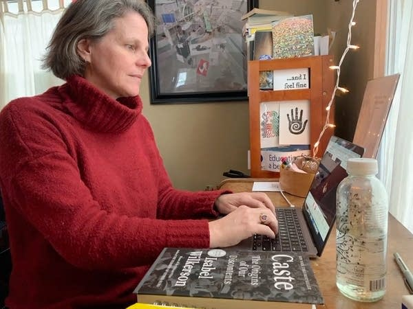 A woman uses a laptop when working at a home office.
