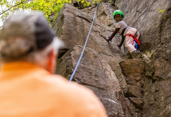 A young girl looks down from an edge while rock climbing.